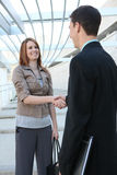 Business Team Handshake. An attractive man and woman business team handshake at the office stock photos