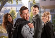 Business team having fun. Portrait of happy business team standing outdoor having fun, sticing out their tongues Stock Photo