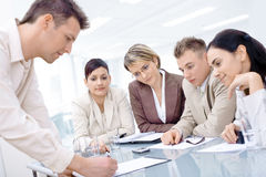 Business team having meeting. Businessman leaning on desk, explaining to four colleagues sitting royalty free stock image