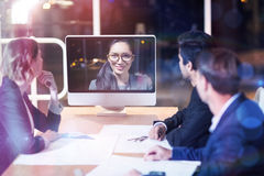 Business team having video conference. 3D Business team having video conference at desk in office Royalty Free Stock Image
