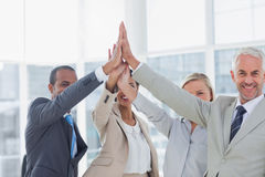 Business team high fiving and smiling at camera Stock Photos