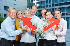 Business team holding arrows as symbol for career. Business team holding big red arrows as symbol for career and success Royalty Free Stock Image