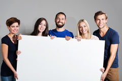 Business team holding a blank sign. Business team or group of diverse young professional friends holding a blank white sign in front of them with friendly smiles Royalty Free Stock Photos