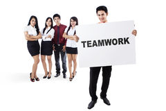 Business team holding a board with teamwork text Stock Image