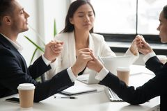 Business team holding hands praying for success. Mixed business team holding hands, meditating, praying for success, managing work stress. Colleagues relaxing stock photos