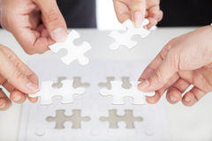 Business team Holding Jigsaw Puzzle on the desk Royalty Free Stock Photography