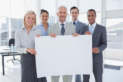 Business team holding large blank poster Royalty Free Stock Photos