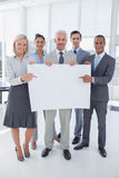 Business team holding large blank poster and smiling at camera Stock Photography