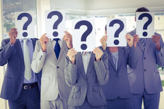 Business team holding question marks over face Stock Images