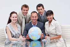 Business team holding a terrestrial globe. In the office. Global business concept stock photos