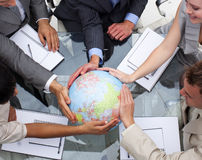 Business team holding a terrestrial globe. High angle of business team holding a terrestrial globe. Global expansion royalty free stock photo