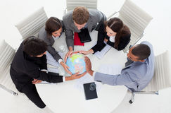 Business team holding a terrestrial globe. International Business team holding a terrestrial globe in a meeting stock images