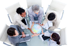Business team holding a terrestrial globe. Serious international business team holding a terrestrial globe in a meeting stock image