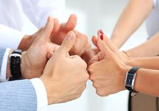 Business team holding their thumbs up. Close-up of business team holding their thumbs up Royalty Free Stock Photography