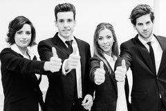Business team holding their thumbs up Royalty Free Stock Image