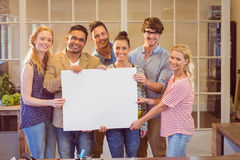 Business team holding a white cardboard Royalty Free Stock Photos
