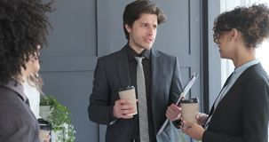Business team interacting while having coffee in office stock footage