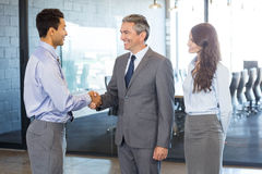 Business team interacting in office. Business team standing together and interacting in office Royalty Free Stock Image