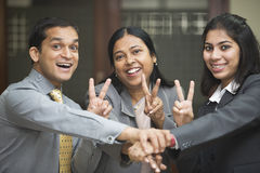 Business team joining hands and showing the victory sign Royalty Free Stock Image