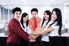 Business team joining their hands in the office Royalty Free Stock Photo