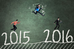 Business team jumps above numbers 2015 to 2016 Stock Photo