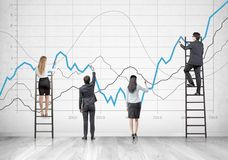 Business team on ladders, graphs Stock Images
