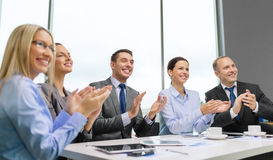 Business team with laptop clapping hands Stock Photo