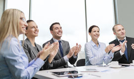 Business team with laptop clapping hands royalty free stock image