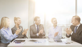 Business team with laptop clapping hands Stock Photography