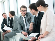 Business team with laptop and documents sitting in the lobby bef Royalty Free Stock Images