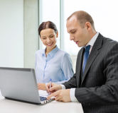 Business team with laptop having discussion. Business, technology and office concept - smiling business team with laptop computer and documents having discussion Stock Photography