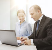 Business team with laptop having discussion. Business, technology and office concept - smiling business team with laptop computer and documents having discussion Royalty Free Stock Image