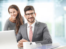 Business team with laptop. Business women and business men working together on laptop while sitting at office Stock Image