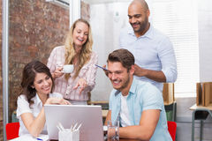 Business team laughing together in front of the laptop Royalty Free Stock Images