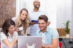 Business team laughing together in front of the laptop Royalty Free Stock Photo