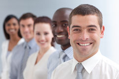 Business team in a line. Business team in a line smiling at the camera. Focus on a young man Royalty Free Stock Photos
