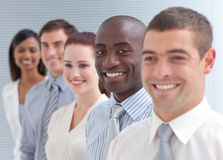 Business team in a line. Business team in a line smiling at the camera. Focus on an Afro-American man Stock Photo