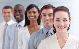 Business team in a line. Business team in a line smiling at the camera. Focus on a beautiful woman Stock Image