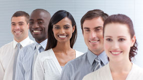 Business team in a line. Business team in a line smiling at the camera. Focus on a Indian woman Stock Photos