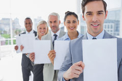 Business team in a line holding blank pages Royalty Free Stock Photos