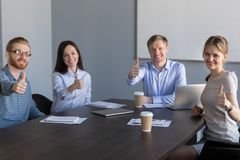 Business team looking at camera showing thumbs up at meeting. Smiling business team sitting at conference table looking at camera showing thumbs up at group royalty free stock images