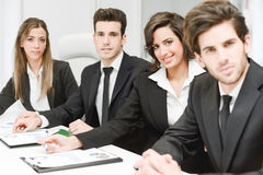 Business team looking at camera in working environment stock images