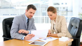Business team looking at documents together at desk. In the office stock video footage