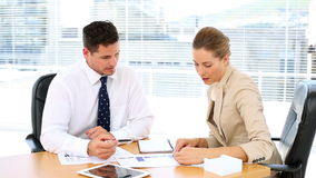 Business team looking at documents together at desk and shaking hands. In the office stock footage