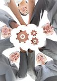 Business team looking down putting hands together behind white cloud and gear graphic and against wh Royalty Free Stock Photos