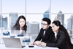 Business team looking at financial chart on laptop Royalty Free Stock Image