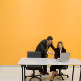 Business team looking at lapto. Man and woman looking at computer screen in office with bright colored walls stock image