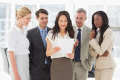 Business team looking at sheet of paper together Stock Photo
