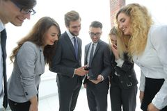 Business team looking at a smartphone screen. Royalty Free Stock Images