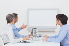 Business team looking at white screen Stock Photography